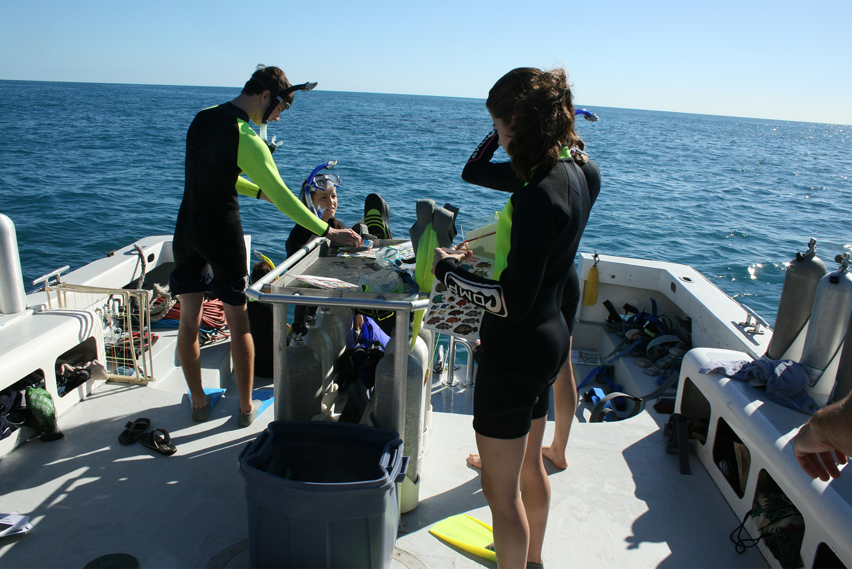 Students with snorkel equipment on a boat in the ocean
