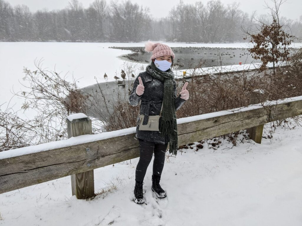 Grace Liu in front of snowy lake giving thumbs' up.