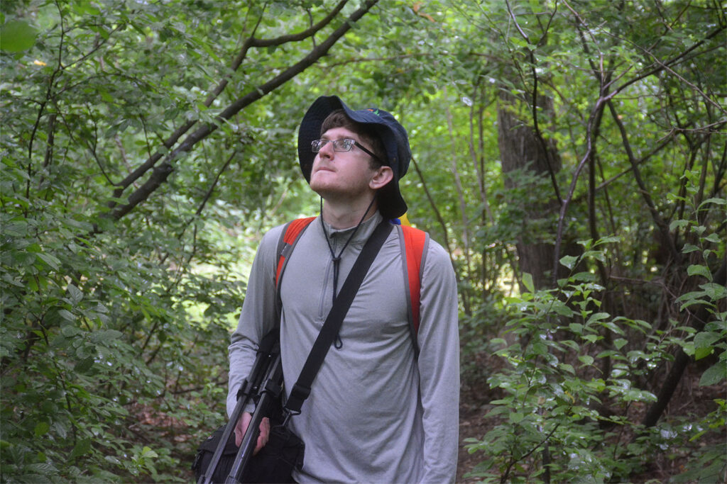 Joe Kawalec in the forest with equipment looking for woodpeckers.