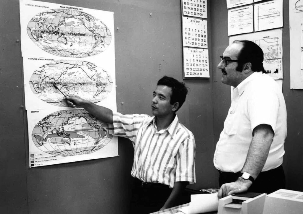 Manabe points at a map with a colleague in the 1960s